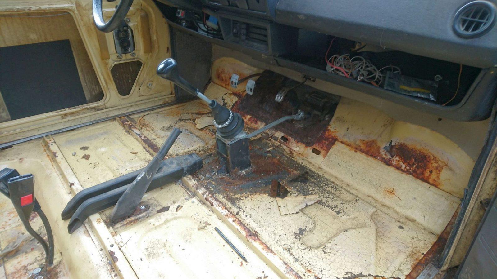 Nachdem mir aufgefallen war, dass die Filzdämmmatten unter dem Teppich etwas feucht waren, entschied ich mich, alles schleunigst aus dem Innenraum zu entfernen. Zum Vorschein kamen einige Roststellen, aber keine wirklichen Durchrostungen. Mal sehen wie das nach dem Sandstrahlen aussehen wird. Besonders interessant ist die notdürftige Reparatur des Schalthebelsockels. Dieser ist wohl im Laufe der Zeit aus Halterung herausgerissen und abgebrochen. Repariert hat man das, indem ein neues Blech eingesetzt und der Sockel an dieses Blech angeschweißt wurde. Insofern ist dieser nicht mehr mit dem Chassis darunter verschraubt und nicht besonders stabil.